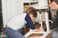 父亲和儿子聚集的家具 免版税库存图片