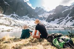 父亲和儿子背包徒步旅行者在山lakeу附近坐包围 免版税库存图片
