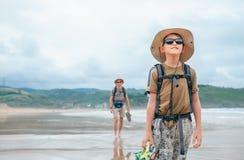 父亲和儿子背包徒步旅行者旅客在沙子海洋海滩走 免版税库存照片
