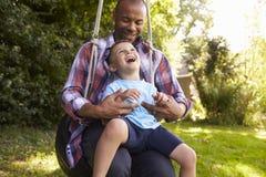 父亲和儿子获得在轮胎摇摆的乐趣在庭院 图库摄影