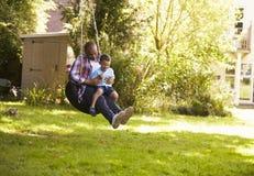 父亲和儿子获得在轮胎摇摆的乐趣在庭院 免版税库存图片