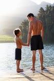 父亲和儿子藏品递在跳船的身分 免版税库存图片