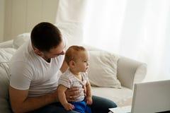 父亲和儿子观看的录影或使用比赛 库存照片