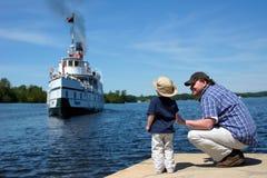 父亲和儿子观看船来端起 免版税库存图片