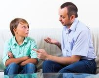 父亲和儿子谈论严肃 库存图片
