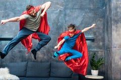 父亲和儿子超级英雄的打扮跳在沙发 库存图片