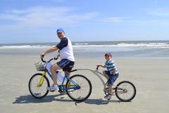 父亲和儿子足迹自行车的在海滩 免版税库存照片