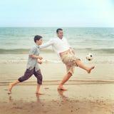 父亲和儿子踢橄榄球的海滩的 免版税库存照片