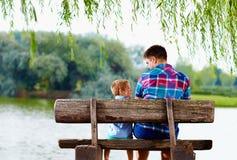 父亲和儿子长凳的在湖附近 免版税库存图片