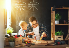 父亲和儿子雕刻了木头在木匠业车间 免版税图库摄影