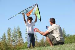 父亲和儿子飞行风筝 免版税库存照片