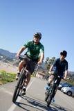 父亲和儿子骑自行车 图库摄影