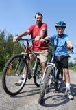 父亲和儿子骑马自行车 免版税库存图片