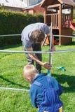 父亲和儿子,当安装大庭院绷床时 免版税库存图片