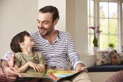 父亲和儿子读书故事在家一起 免版税库存照片