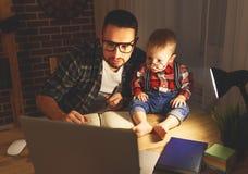 父亲和儿子婴孩在家工作在黑暗的计算机 免版税库存照片