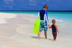 父亲和儿子去游泳在海滩 免版税库存图片