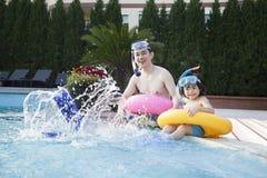 父亲和儿子画象坐由水池和飞溅的边缘的潜航的齿轮的 库存照片