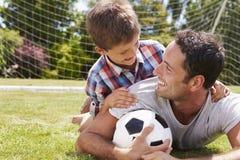 父亲和儿子画象有橄榄球的 库存图片