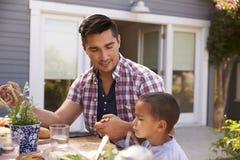 父亲和儿子说雍容在室外膳食前在庭院里 免版税图库摄影