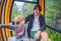 父亲和儿子滑雪电缆车客舱的在夏天 缆车的乘客 库存图片