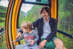 父亲和儿子滑雪电缆车客舱的在夏天 cabl的乘客 库存照片