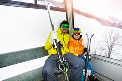 父亲和儿子滑雪电缆车客舱的 库存照片