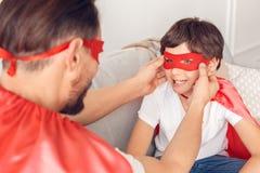 父亲和儿子superheroe服装的在家坐把面具放的沙发人在男孩微笑的特写镜头上 免版税库存图片