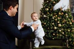 父亲和儿童游戏圣诞节 爸爸拿着他的胳膊的一个男孩在白色滑子 企业父亲 免版税库存图片