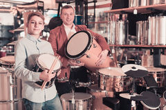父亲和十几岁的儿子审查的磁鼓单元在吉他商店 免版税库存照片