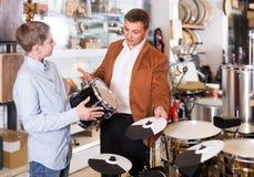 父亲和十几岁的儿子审查的磁鼓单元在吉他商店 库存图片