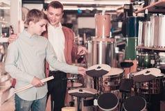父亲和十几岁的儿子审查的磁鼓单元在吉他商店 免版税库存图片