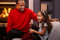 父亲和圣诞节时间的愉快的矮小的女儿 免版税库存图片