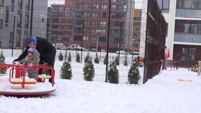 父亲和在圈子的女婴旋转在操场摇摆在冬天围场 4K 股票视频