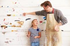 父亲和女儿反对油漆在艺术演播室盖了墙壁 免版税图库摄影