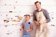 父亲和女儿反对油漆在艺术演播室盖了墙壁 库存图片