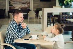 父亲和女儿吃午餐一起在购物中心 库存照片