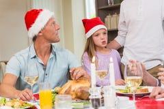 父亲和女儿圣诞老人帽子的在圣诞节时间 库存照片