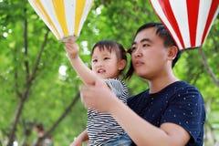 父亲和女儿在公园演奏并且获得乐趣在夏天晴天愉快的孩子本质上 库存照片