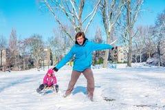 父亲和女儿在冬天公园 库存照片