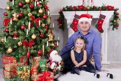 父亲和女儿在圣诞树附近坐 父亲有在他的头的一个圣诞老人帽子 在他们后的一个壁炉 免版税库存图片