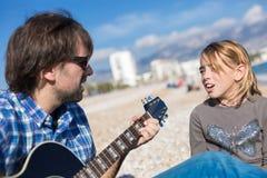 父亲和女儿在海滩的唱歌歌曲 图库摄影