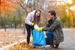父亲和女儿在秋天停放得户外,清扫垃圾 免版税库存图片