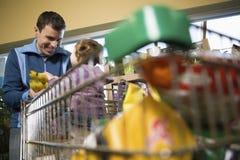 父亲和女儿在超级市场 库存照片