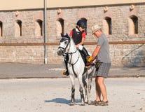 父亲和女儿在超越障碍马术比赛竞争前 免版税库存照片