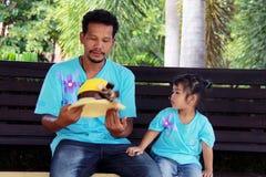 父亲和女儿坐长凳 免版税库存图片