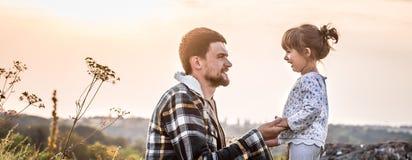 父亲和女儿日落的,家庭价值观 免版税库存图片