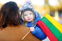 父亲和女儿有一面旗子的在拿着三色立陶宛旗子的立陶宛独立日 免版税库存照片