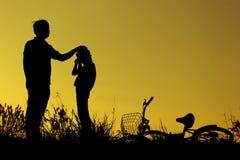 父亲和女儿有乐趣骑马自行车在日落,活跃家庭体育,活跃孩子炫耀,亚洲孩子,在su现出轮廓孩子 免版税库存图片