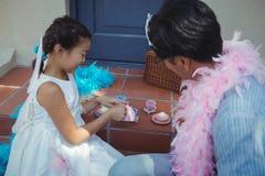 父亲和女儿有神仙的服装的茶会 图库摄影
